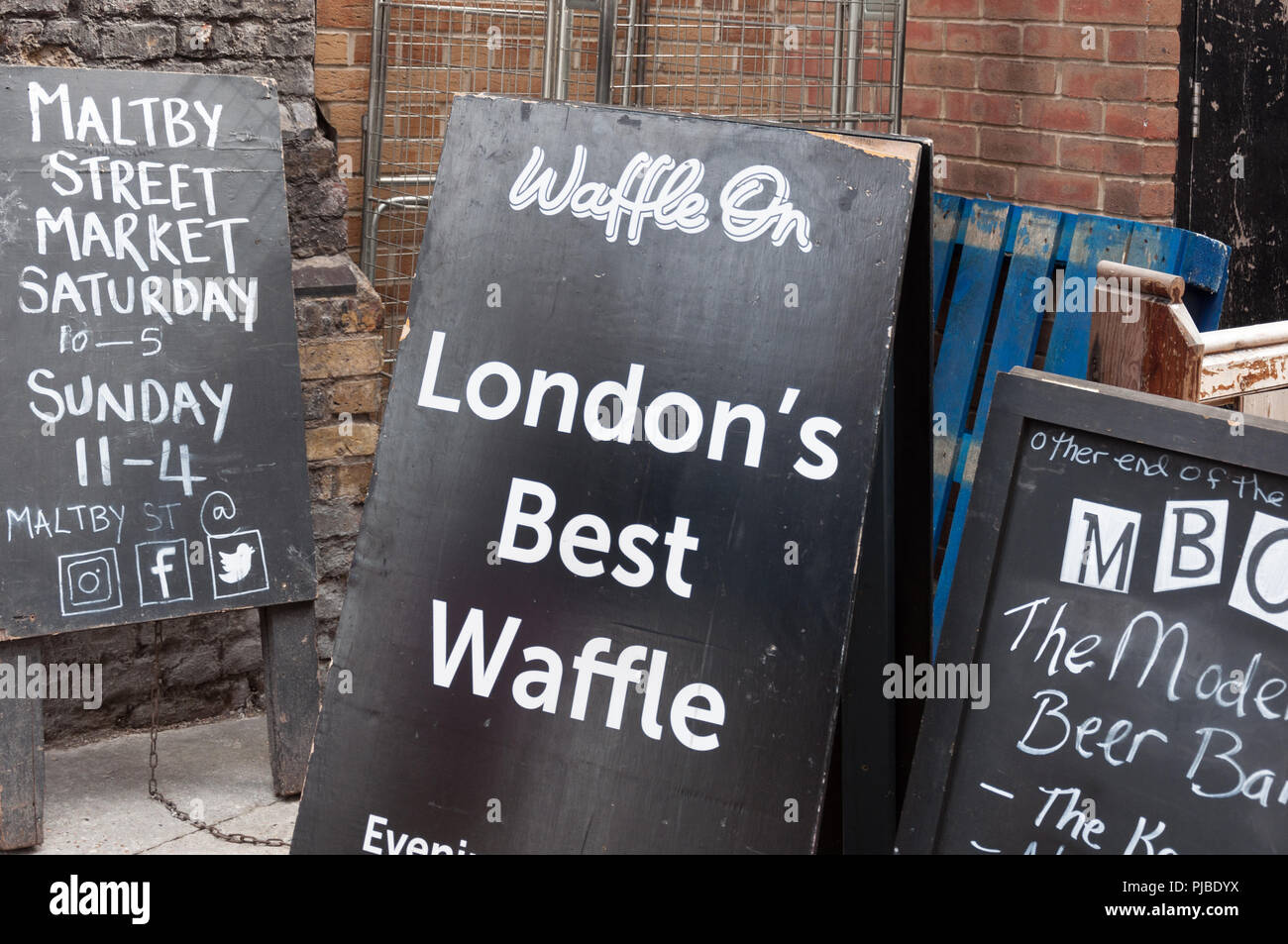 Advertisement blackboards at the entrance to Maltby Street Market, London, England, UK - Stock Image