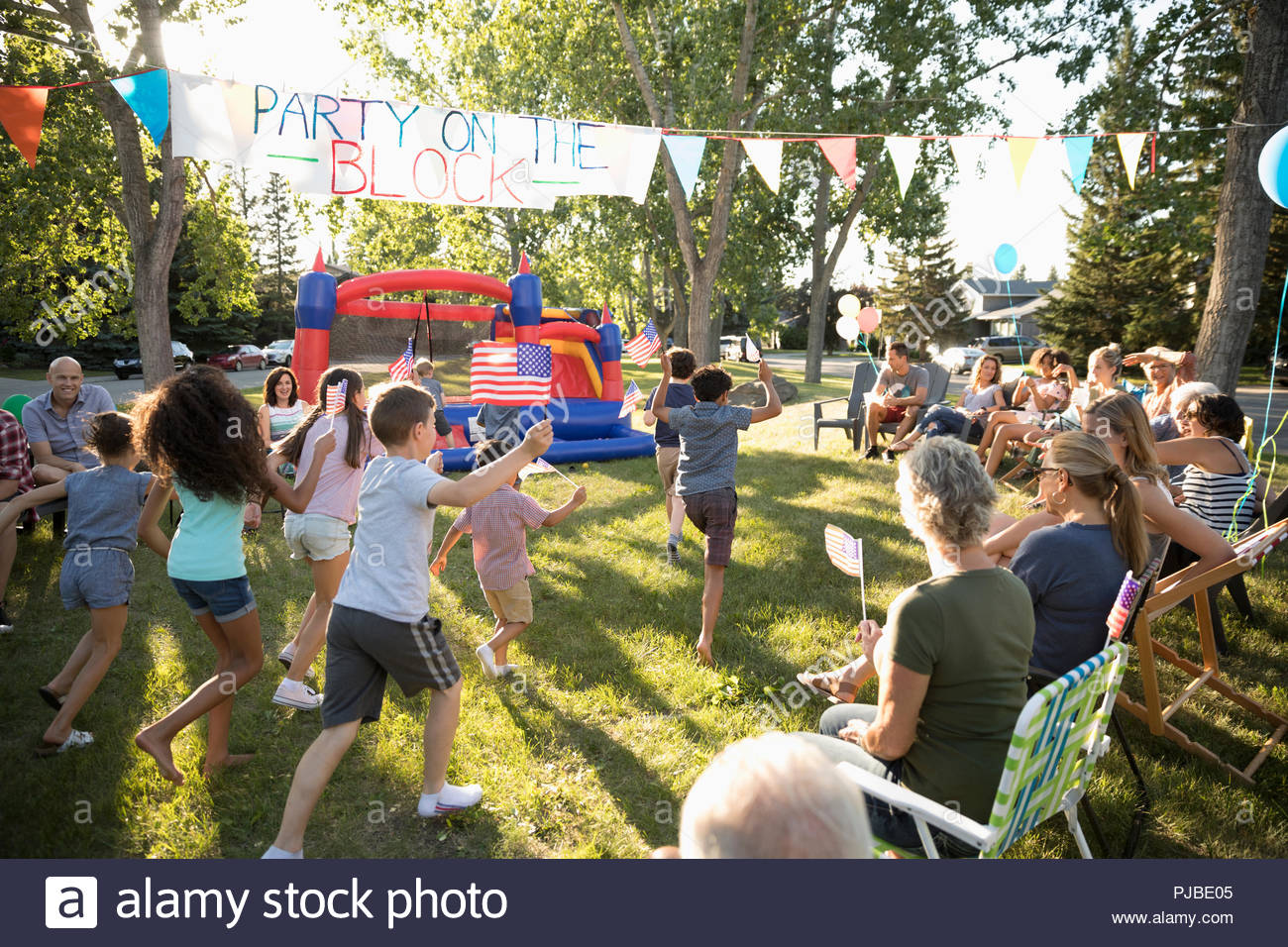 Neighbors watching kids waving American flags at 4th of July summer neighborhood block party in sunny park - Stock Image