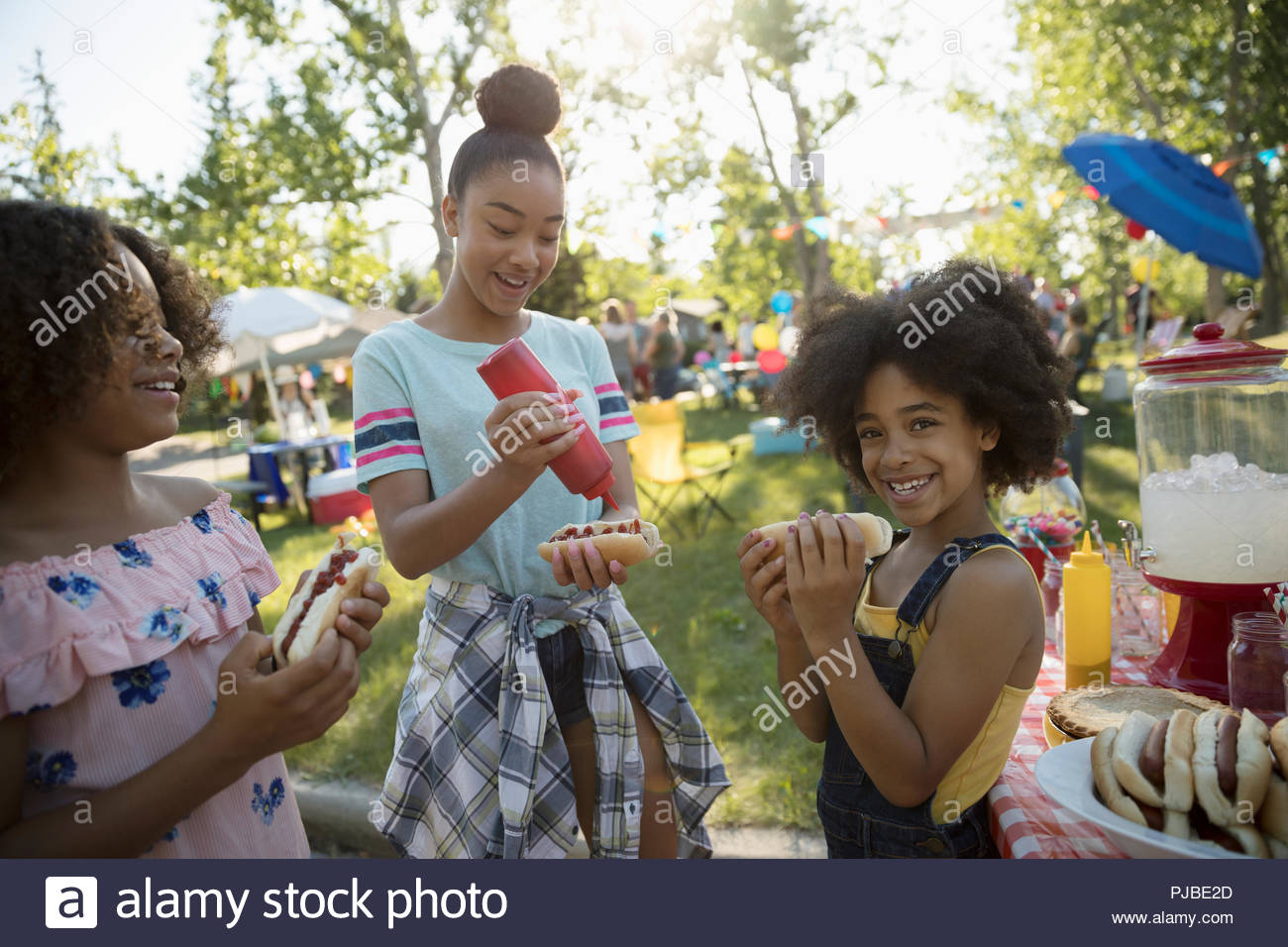 Sisters eating hot dogs at summer neighborhood block party in park Stock Photo