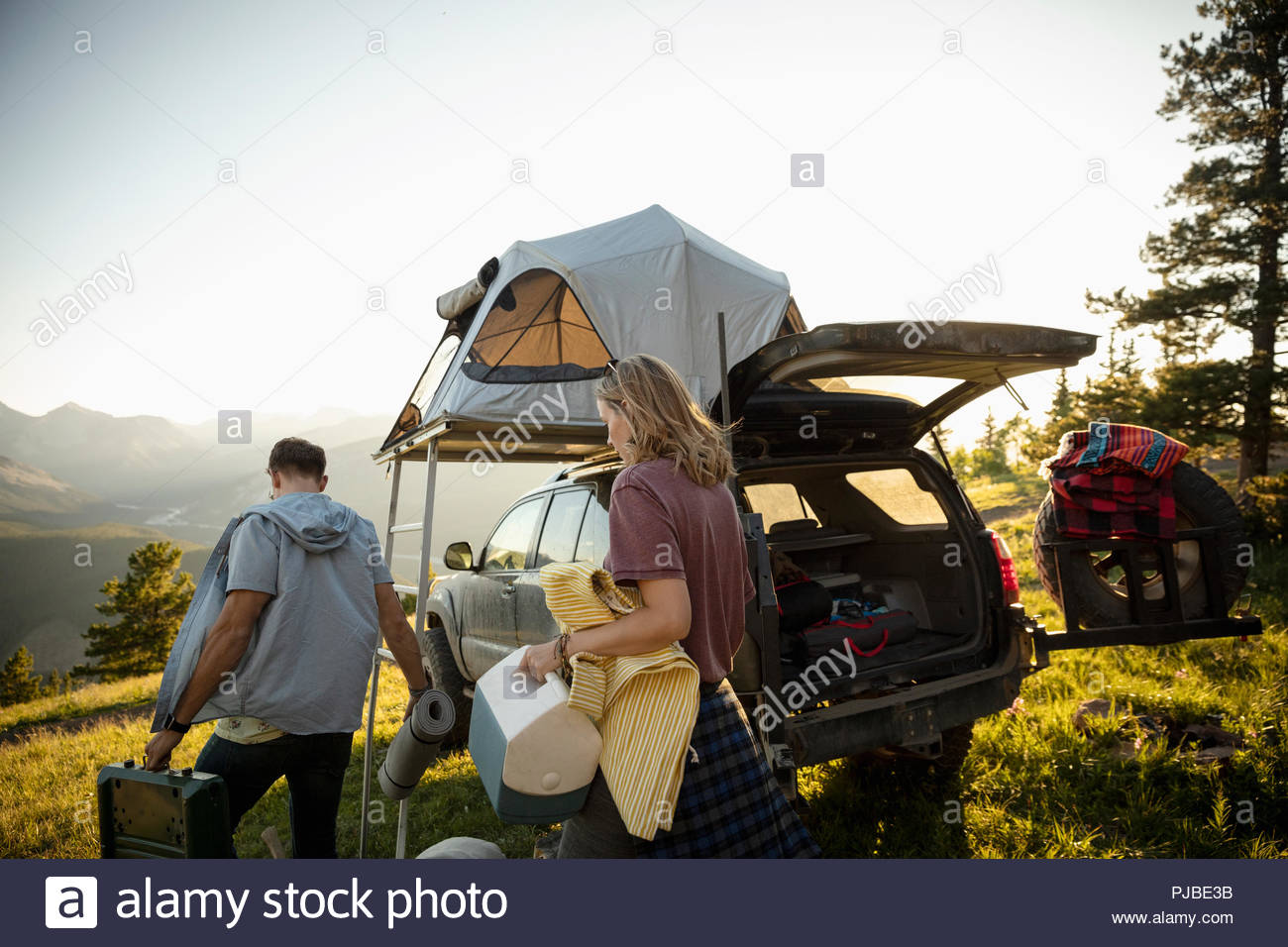 Couple c&ing unloading SUV with rooftop tent in sunny field Alberta Canada & Couple camping unloading SUV with rooftop tent in sunny field ...