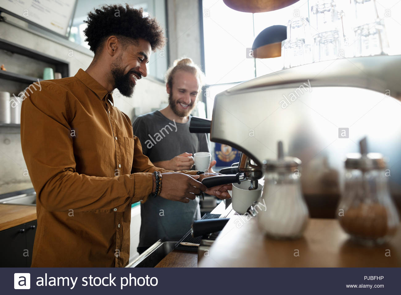 Baristas making espresso drinks in cafe - Stock Image