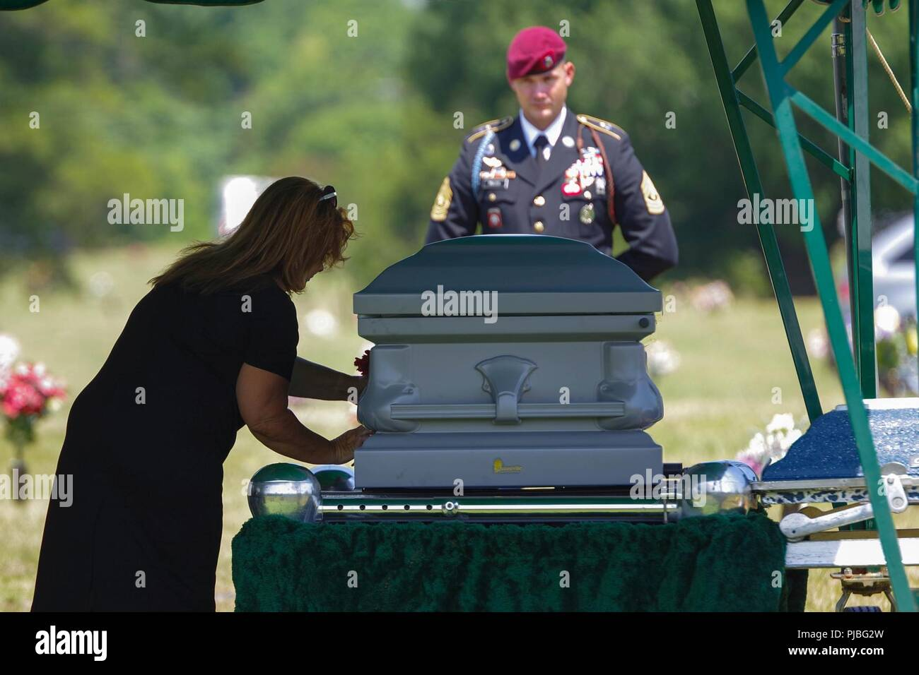 A family member of retired 1st Sgt. Harold Eatman, left, places a flower on his casket at Sharon Memorial Park in Charlotte, North Carolina on July 11 as 1st Sgt. James Miller, right, of Company, B, 2nd Battalion, 505th Parachute Infantry Regiment looks on.  Eatman was a member of the 505th PIR during World War II, making combat jumps into Sicily, Salerno, Normandy and Holland.  Eatman passed away earlier in July at the age of 102. Stock Photo