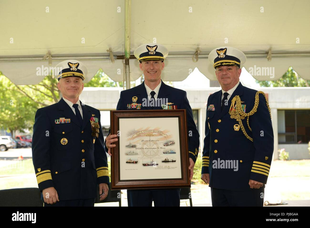 Rear Adm. David Throop, commander Coast Guard 13th District and Capt. Brendan McPherson, chief of staff Coast Guard 13th District, presents a Master Cutterman certificate to Chief Warrant Officer Christopher Boss during a ceremony held at Marine Safety Unit Portland, Ore., July 12, 2018.    The Master Cutterman certificate is earned by serving an accumulative of 20 years  at sea serving aboard Coast Guard cutters.    U.S. Coast Guard - Stock Image