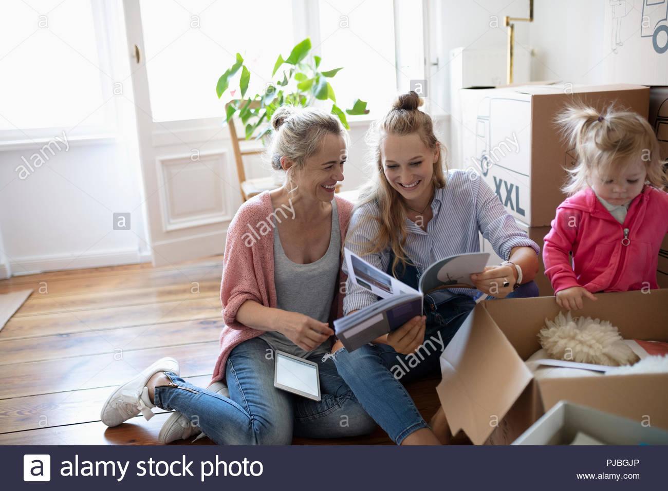 Multi-generation family unpacking, reading book - Stock Image