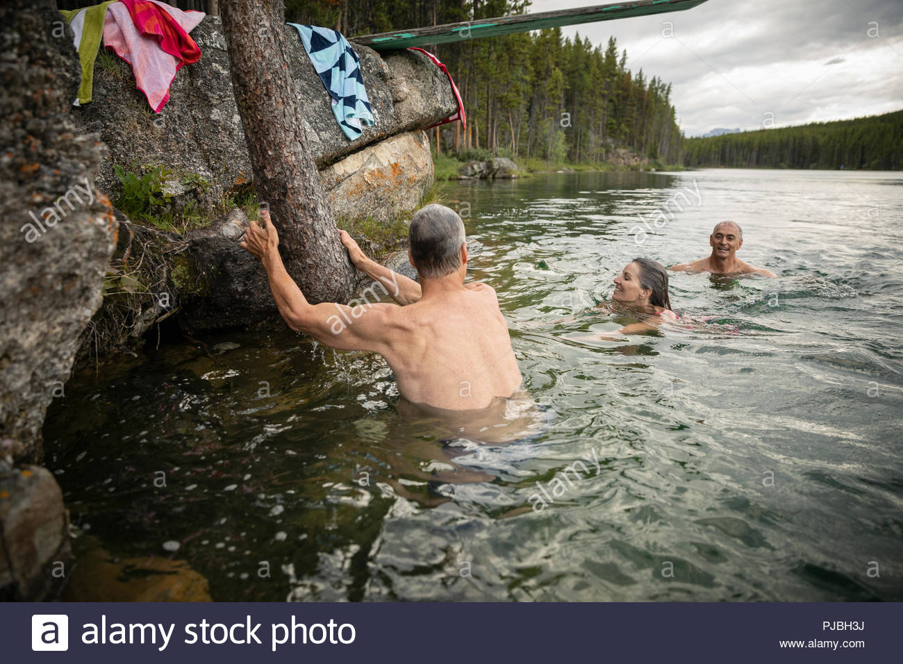 Mature friends swimming in lake - Stock Image