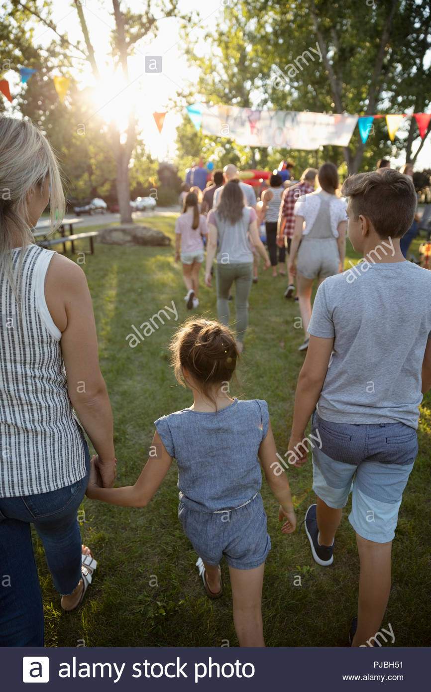 Family arriving at summer neighborhood block party in park - Stock Image