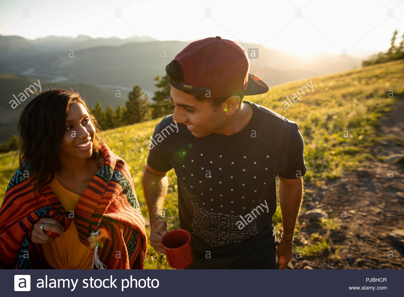 Couple drinking coffee on sunny hill - Stock Image