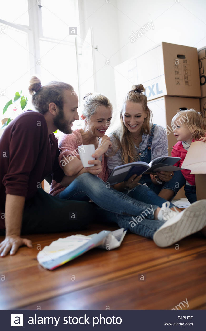 Multi-generation family reading book, taking a break from moving - Stock Image