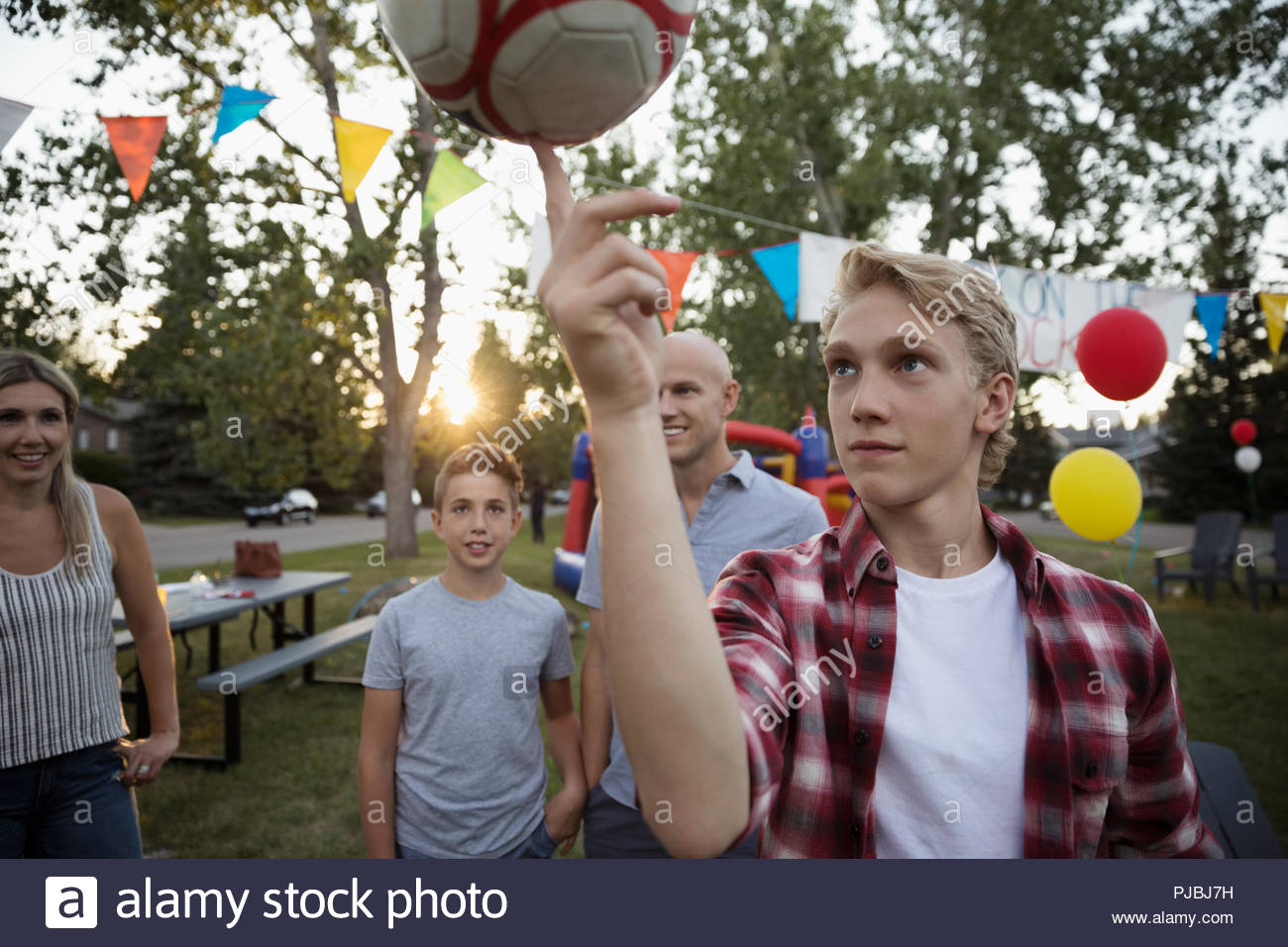 Boy balancing soccer ball on finger at summer neighborhood block party in park - Stock Image