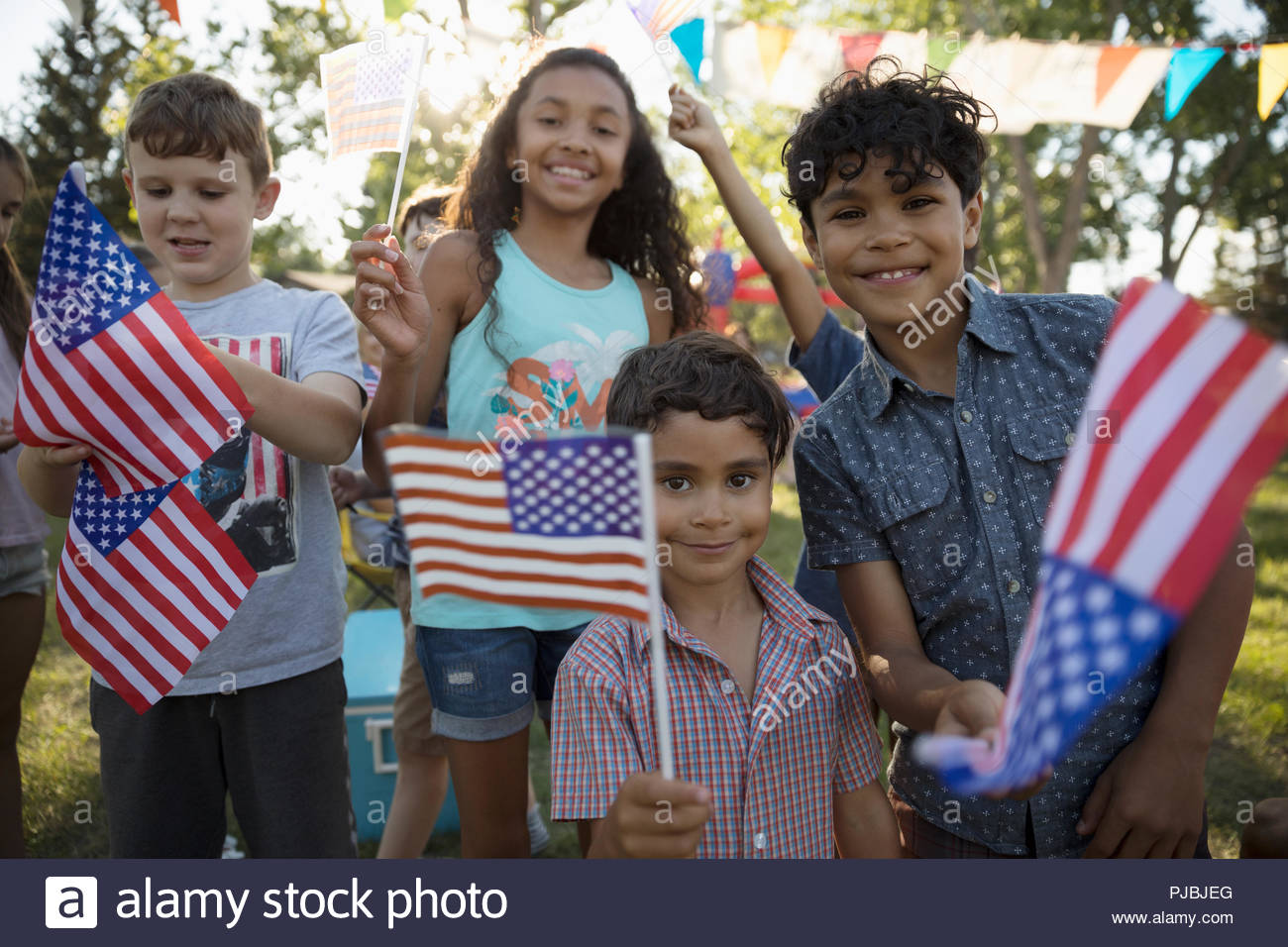 Portrait kids waving 4th of July American flags in park - Stock Image