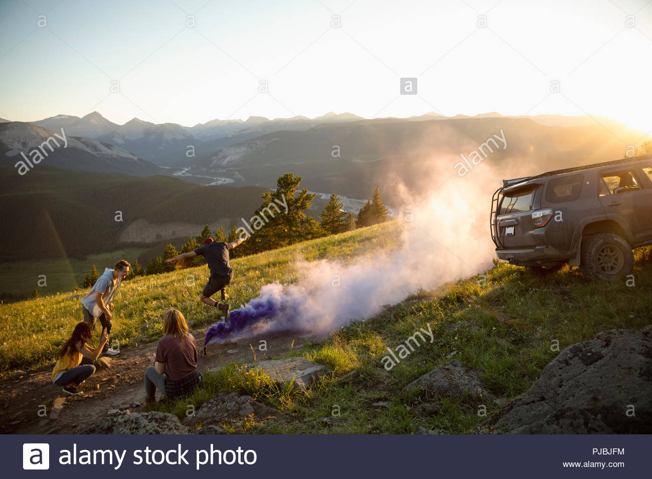 Friends camping, playing with colorful smoke bombs in sunny, idyllic mountain field, Alberta, Canada - Stock Image