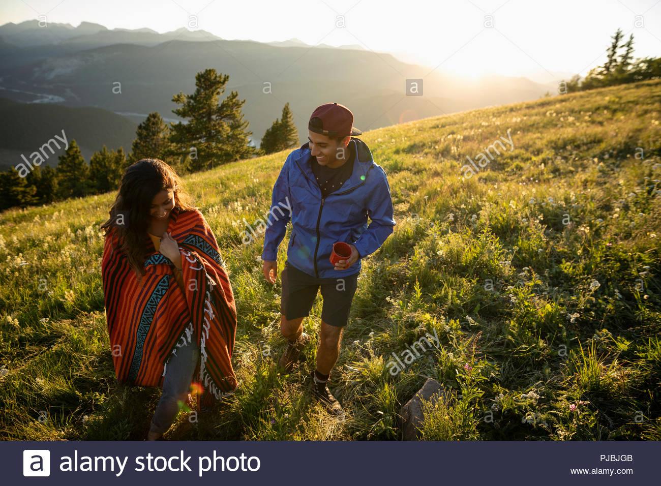 Couple with coffee and blanket walking on sunny, idyllic mountain hillside, Alberta, Canada - Stock Image