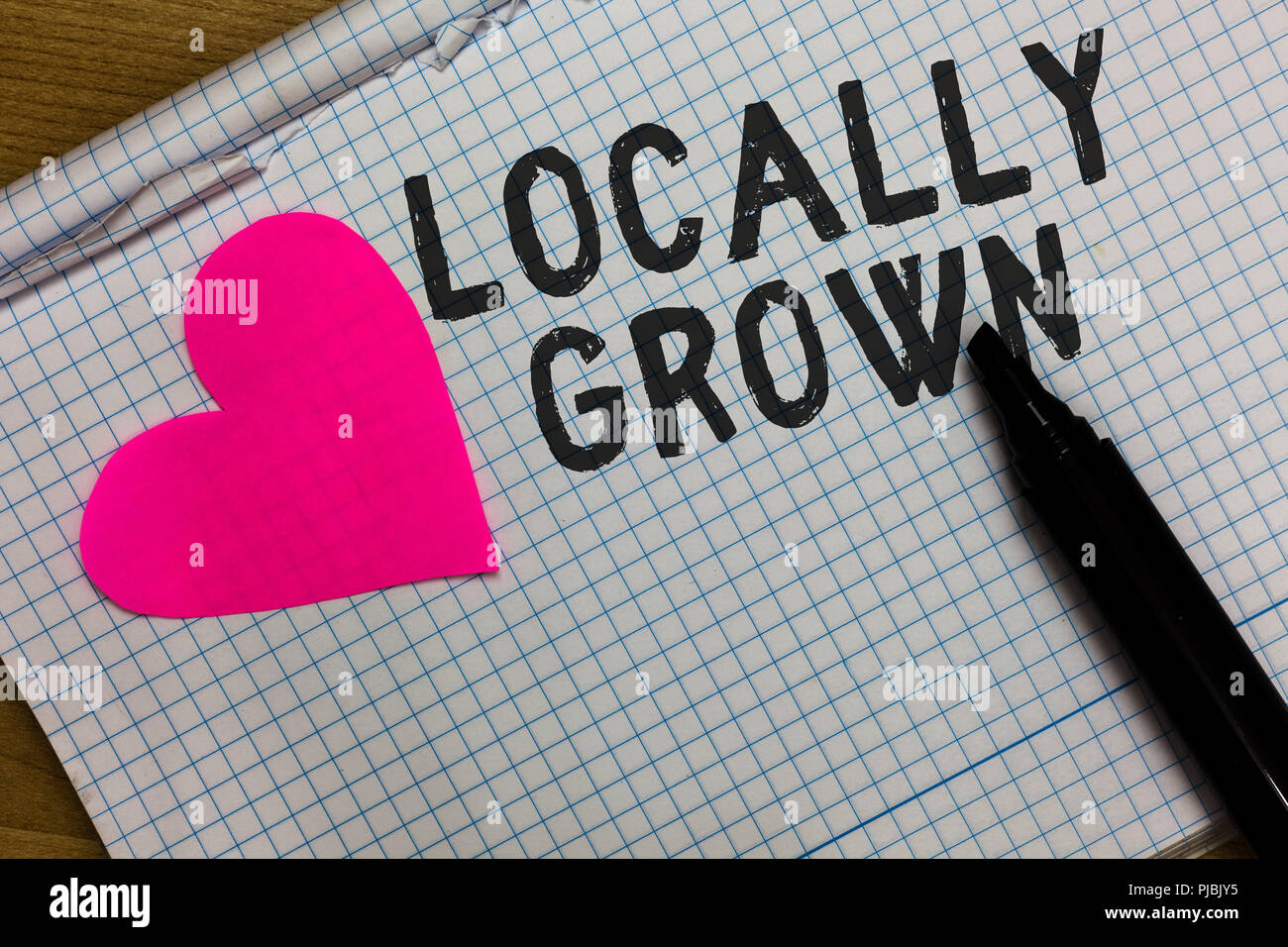 Text sign showing Locally Grown. Conceptual photo Produced Agricultural Countryside Fresh Vegetables Squared notebook paper ripped sheets Marker roman - Stock Image