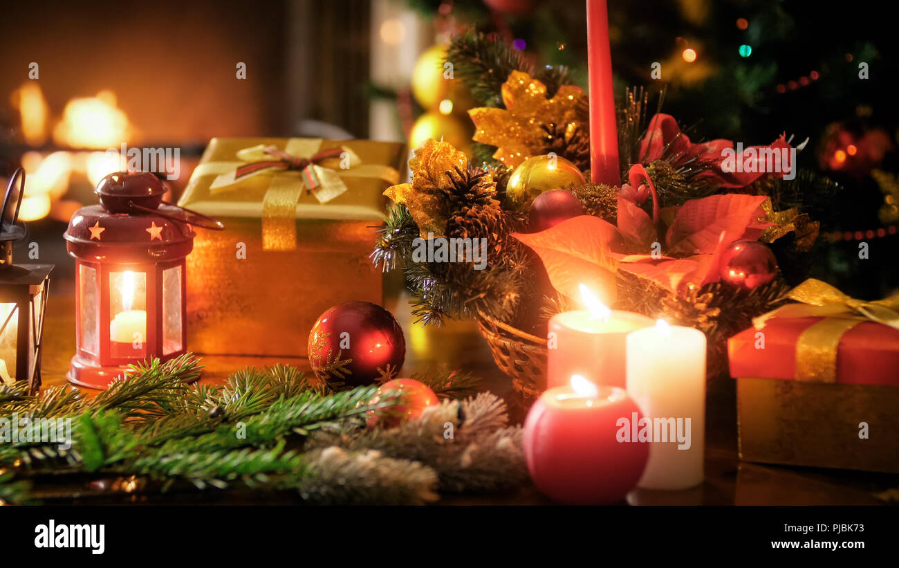 closeup image of traditional wreath gift boxes and lanterns against christmas tree and fireplace