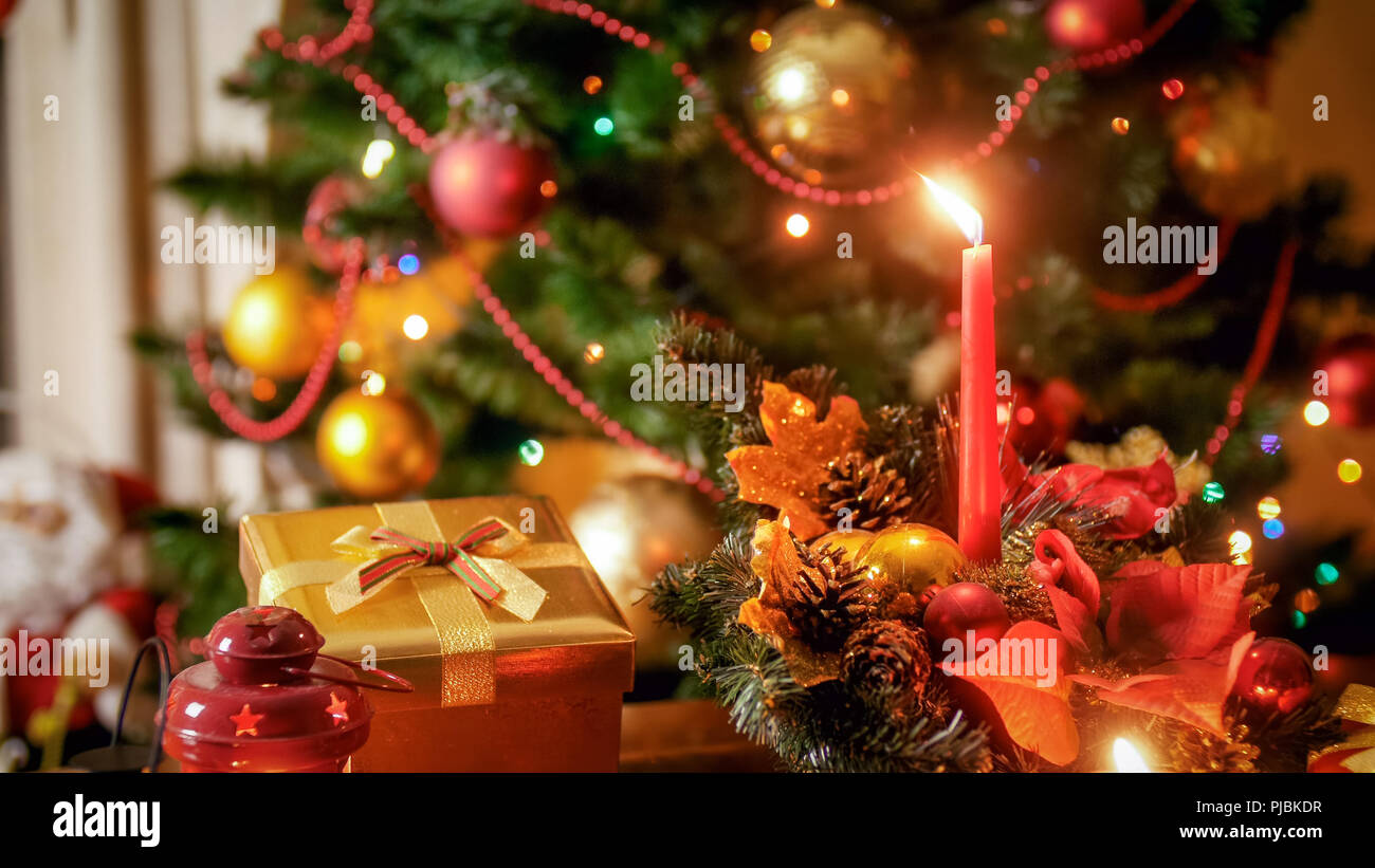 closeup image of burning candles and gift box against christmas tree at night stock image
