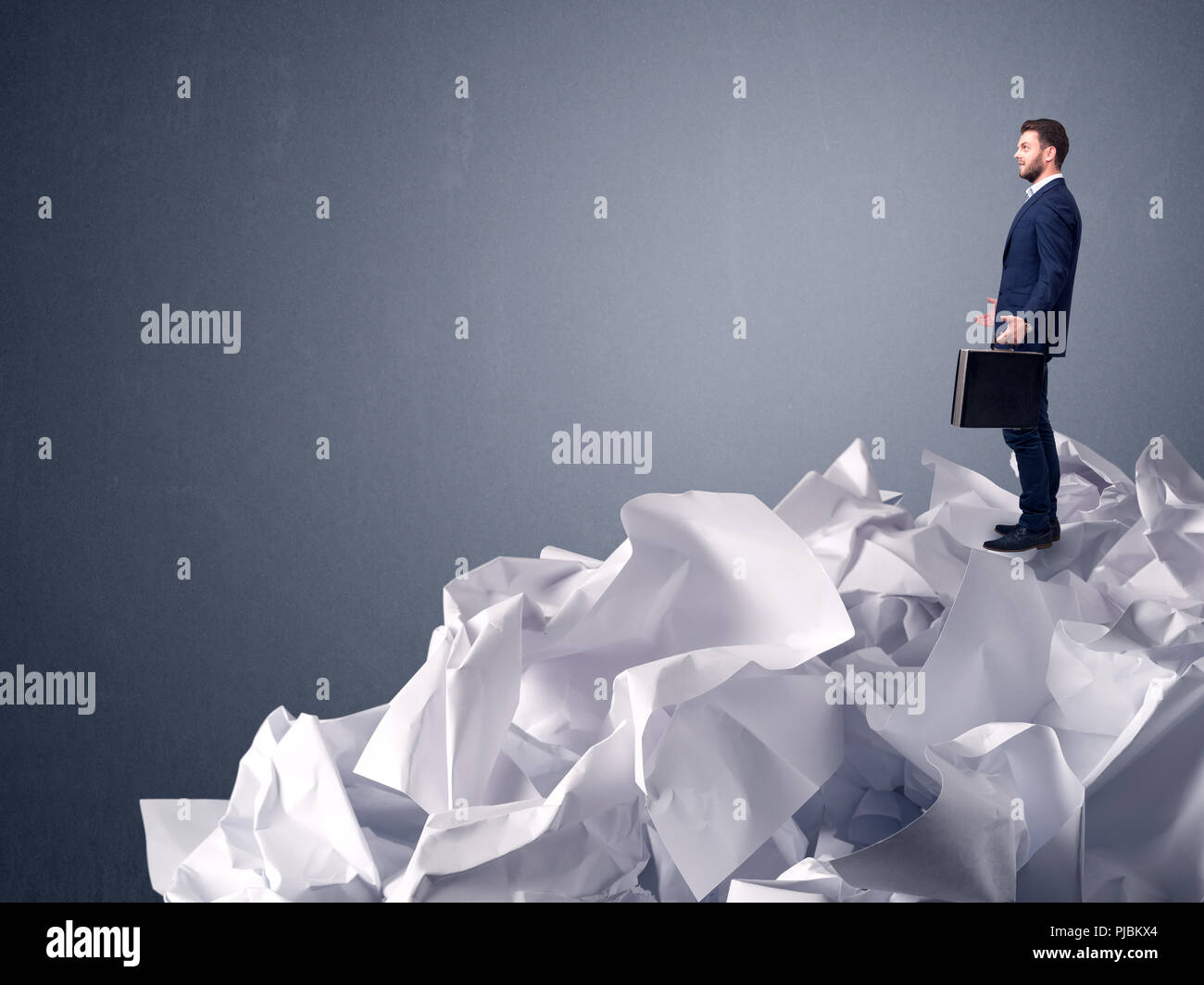 Thoughtful young businessman standing on a pile of crumpled paper with a light grey background - Stock Image
