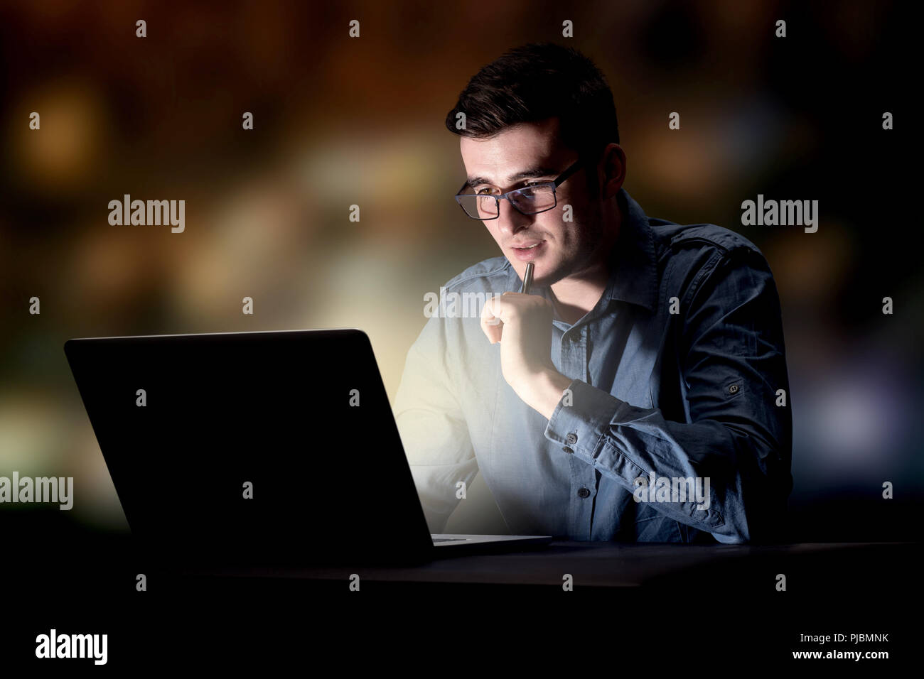 Young handsome businessman working late at night in the office - Stock Image