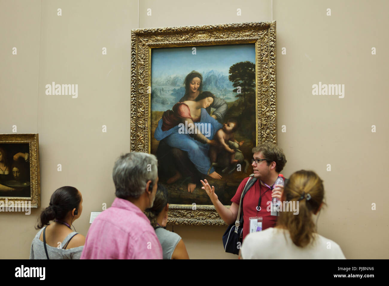 Guided tour in front of the painting 'Virgin and Child with Saint Anne' by Italian Renaissance painter Leonardo da Vinci (ca. 1503) displayed in the Louvre Museum in Paris, France. - Stock Image