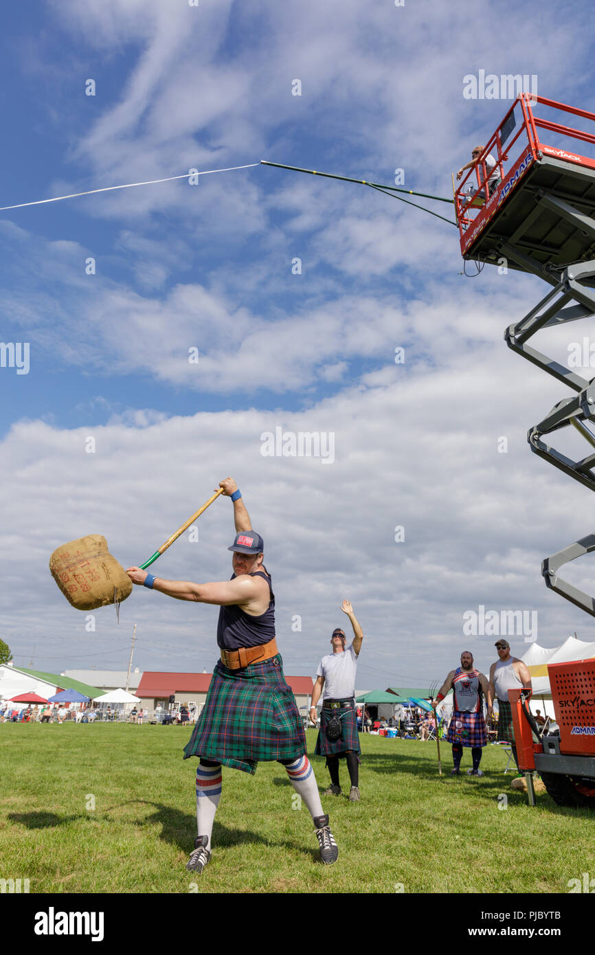 Man competes in the sheaf toss at the annual Capital District Scottish Games in Altamont, New York - Stock Image