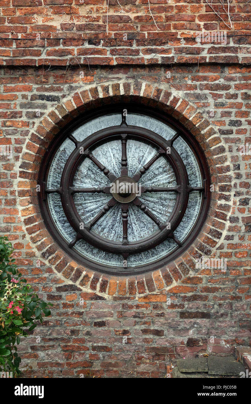 one round exterior wheel window built into a house red brick wall PJC05B