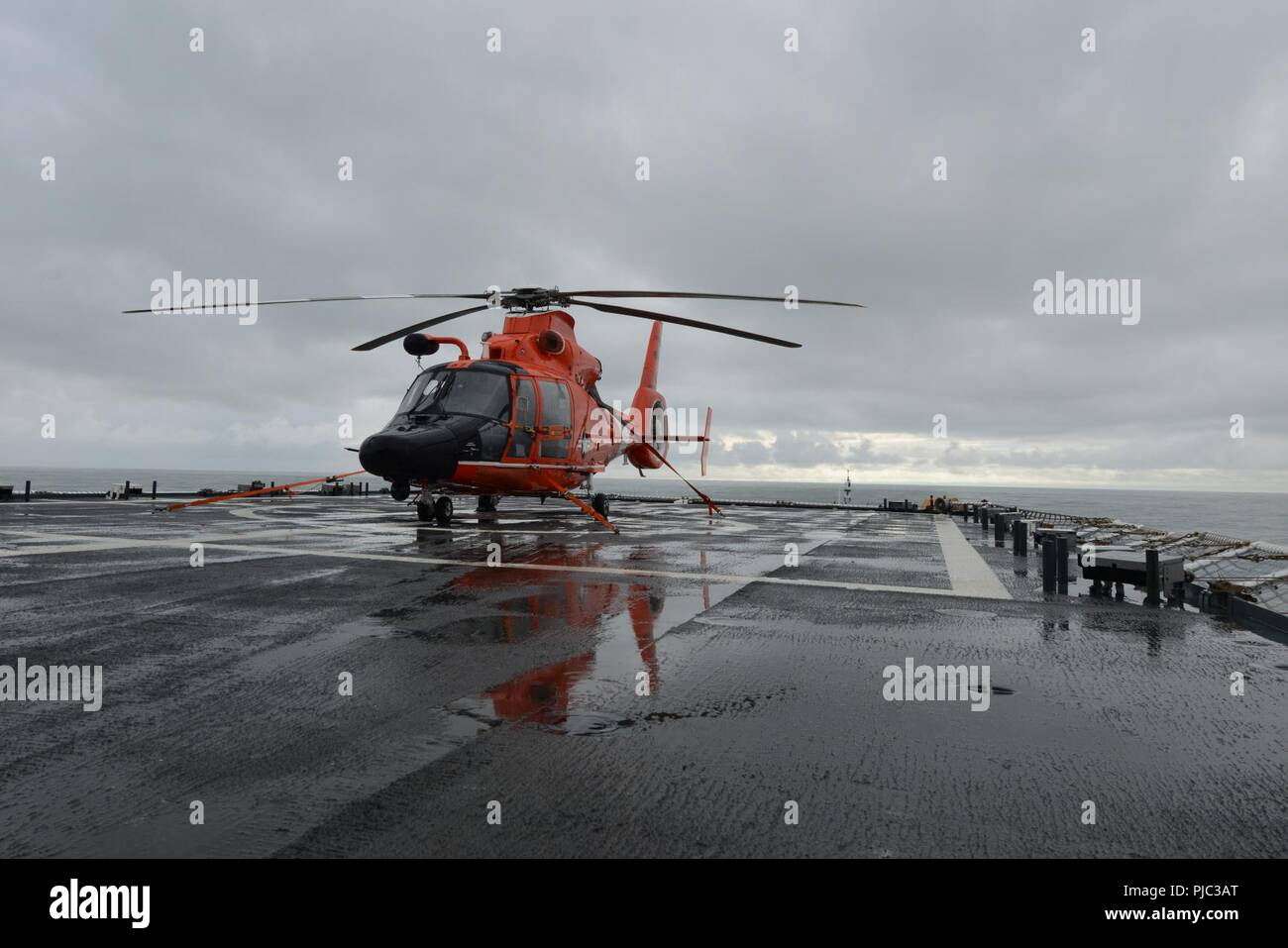 An MH-65 Dolphin helicopter, embarked aboard the Coast Guard