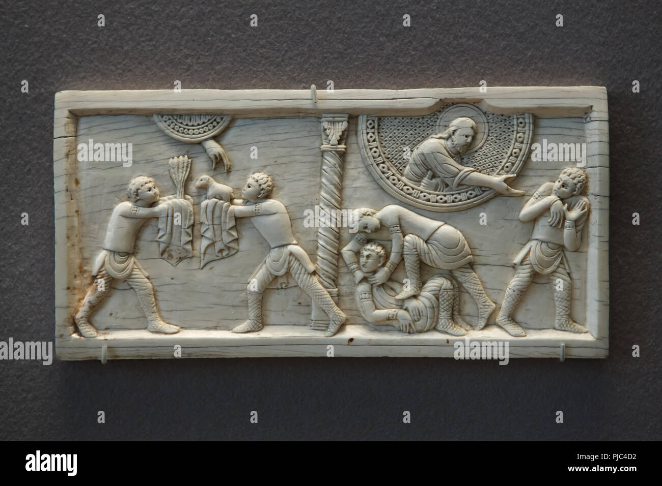 Story of Cain and Abel depicted in the ivory plaque from the Salerno Cathedral (ca. 1084) on display in the Louvre Museum in Paris, France. The Sacrifice of Cain and Abel (L) and Cain slaying Abel (R) are depicted in the plaque. - Stock Image