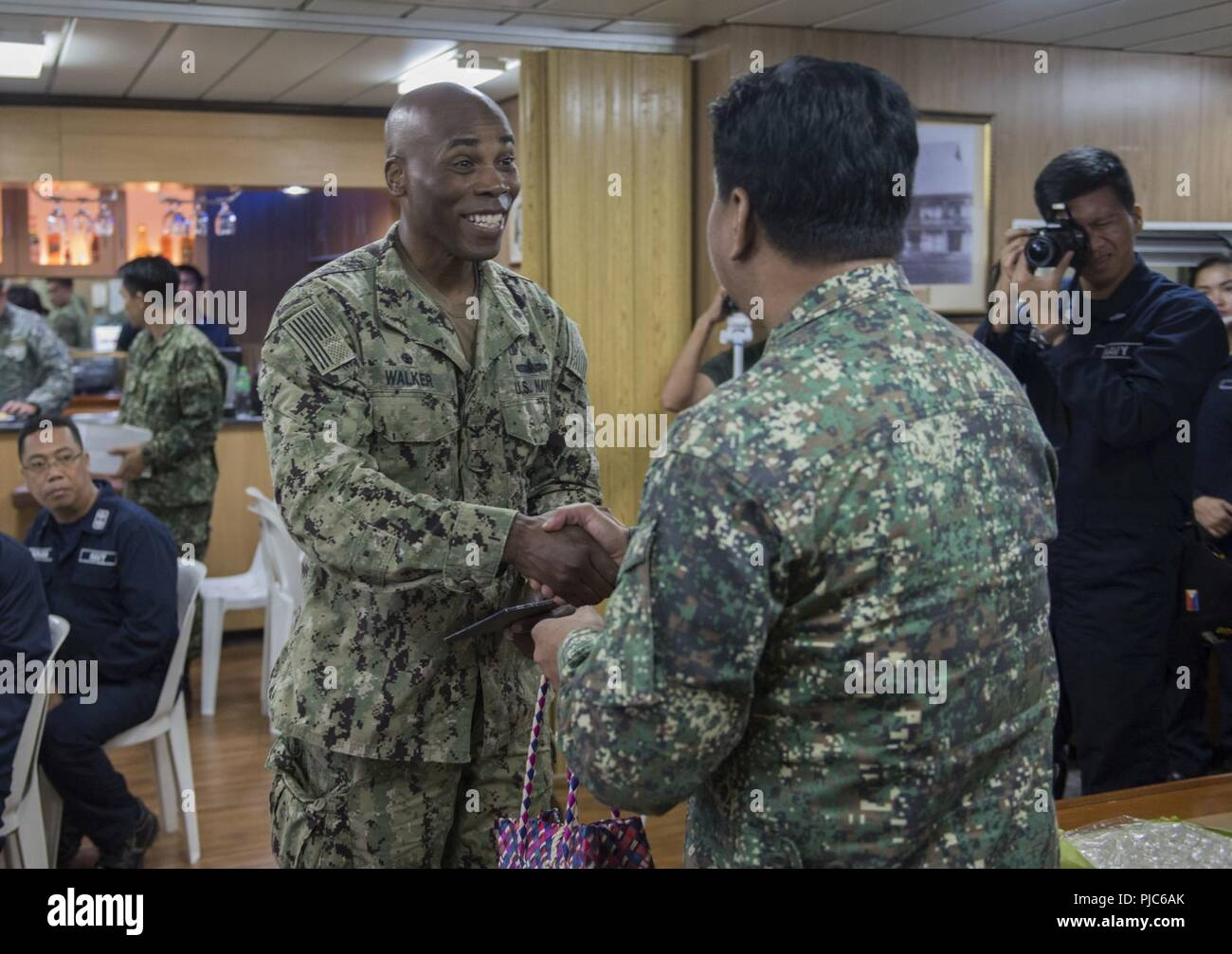 SAN FERNANDO CITY, Philippines (July 14, 2018) Capt. Lex Walker, Commodore, Destroyer Squadron 7, exchanges gifts with Philippine Navy Commodore Nichols Driz, Commander, Naval Forces Northern Luzon, at the closing ceremony of Maritime Training Activity (MTA) Sama Sama 2018 aboard Philippine Navy ship BRP Tarlac (LD-601). The week-long engagement focuses on the full spectrum of naval capabilities and is designed to strengthen the close partnership between both navies while cooperatively ensuring maritime security, stability and prosperity. Stock Photo