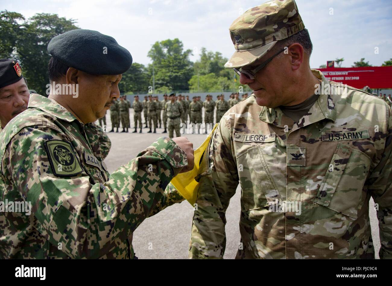 Maj. Gen. Dato HJ Azlan bin Abu Rahman, Chief of Staff, Army Field Command, West Headquarters, Malaysian Army, places a brassard on Col. Anthony Lieggi, Commander, 96th Troop Command, Washington Army National Guard, at the opening ceremony for Exercise Keris Strike, July 23, 2018. Exercise Keris Strike is a bilateral exercise between Malaysia and the U.S., with an emphasis on regional humanitarian assistance and disaster relief operations. Stock Photo