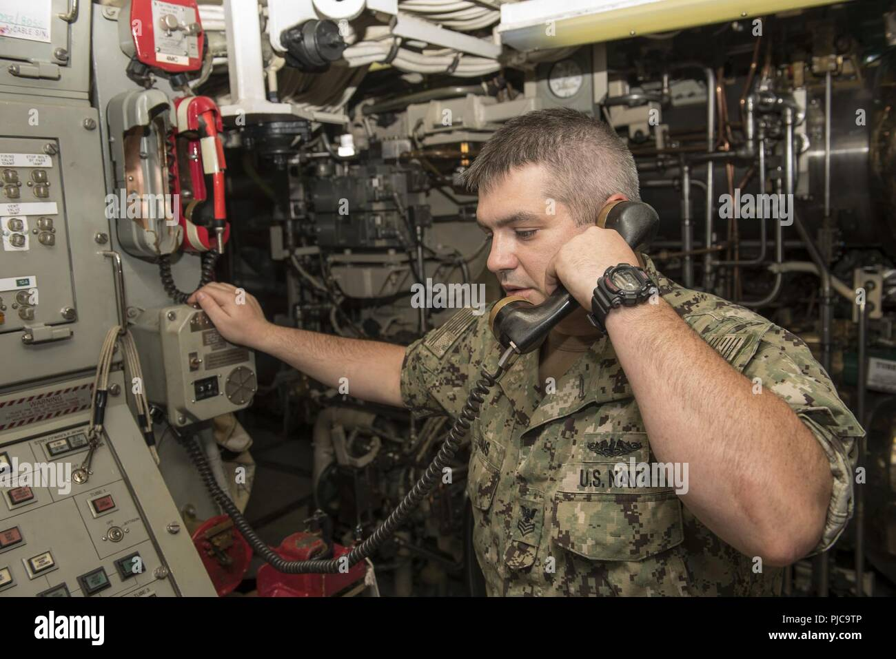Machinist's Mate (Non-Nuclear, Submarine Weapons) 1st Class Norman Williams uses a sound-powered telephone in the torpedo room of the Ohio-class ballistic missile submarine USS Alaska (SSBN 732). Alaska is conducting routine maintenance inport at Naval Submarine Base Kings Bay. - Stock Image