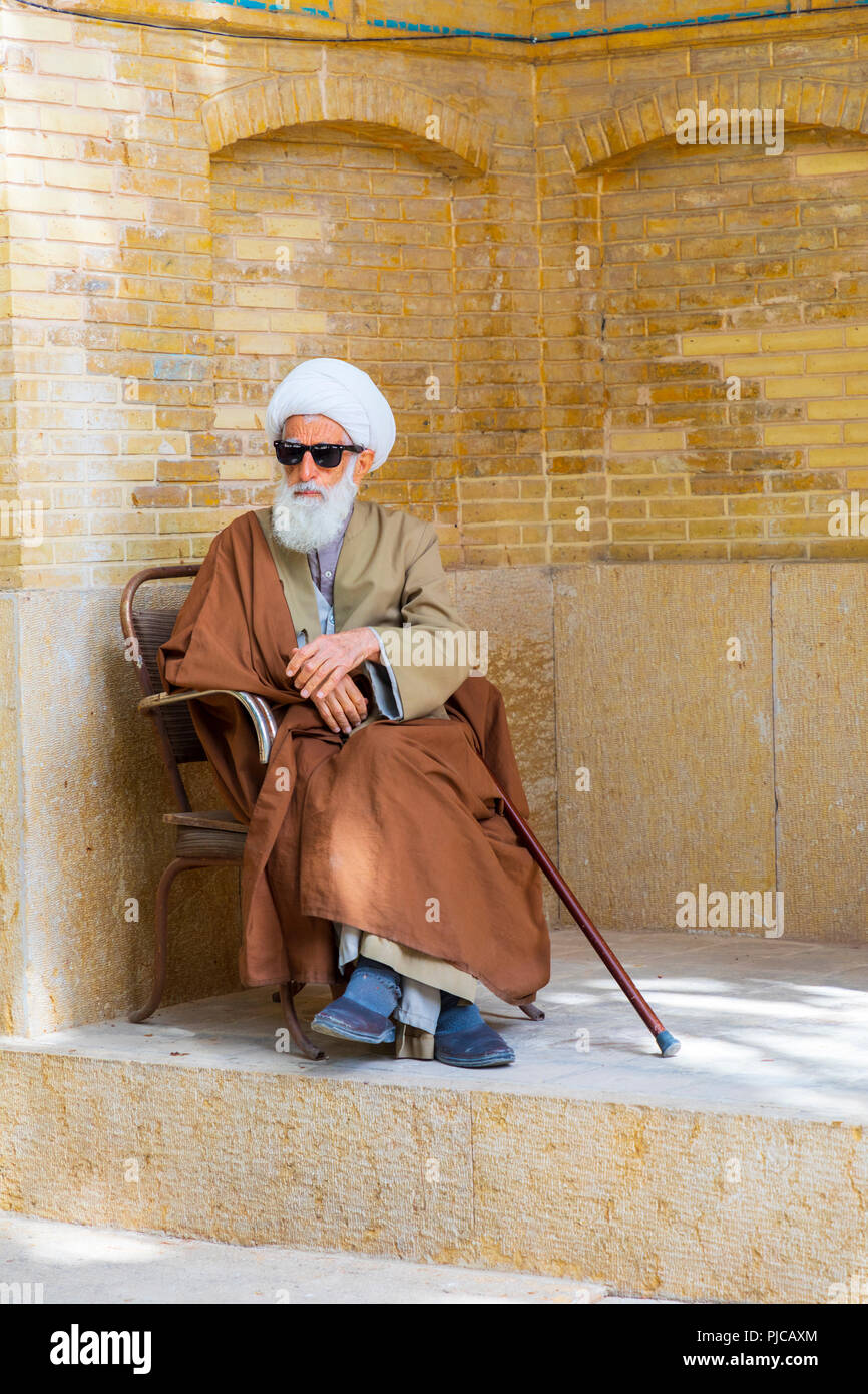 Islamic Republic of Iran. Shiraz. An Ayatollah (Shiite Cleric) sitting near the Khan Madrassah.  March 08, 2018 - Stock Image