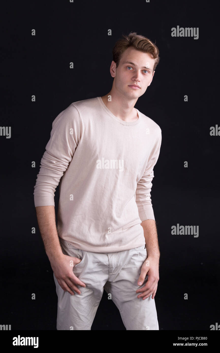 Handsome Male Model With Blue Eyes And Light Curlie Hair In Beige Sweater And White Pants On A Dark Background Stock Photo Alamy