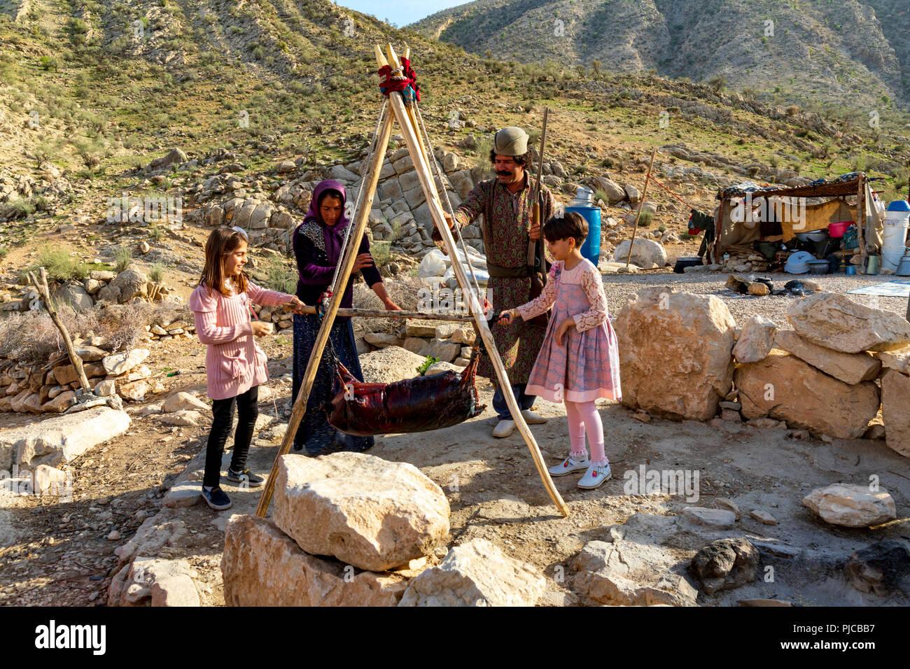 Islamic Republic of Iran. . Fars Province, Rudbal. Qashqai nomads churning butter in animal skin bag.  March 10, 2018 - Stock Image