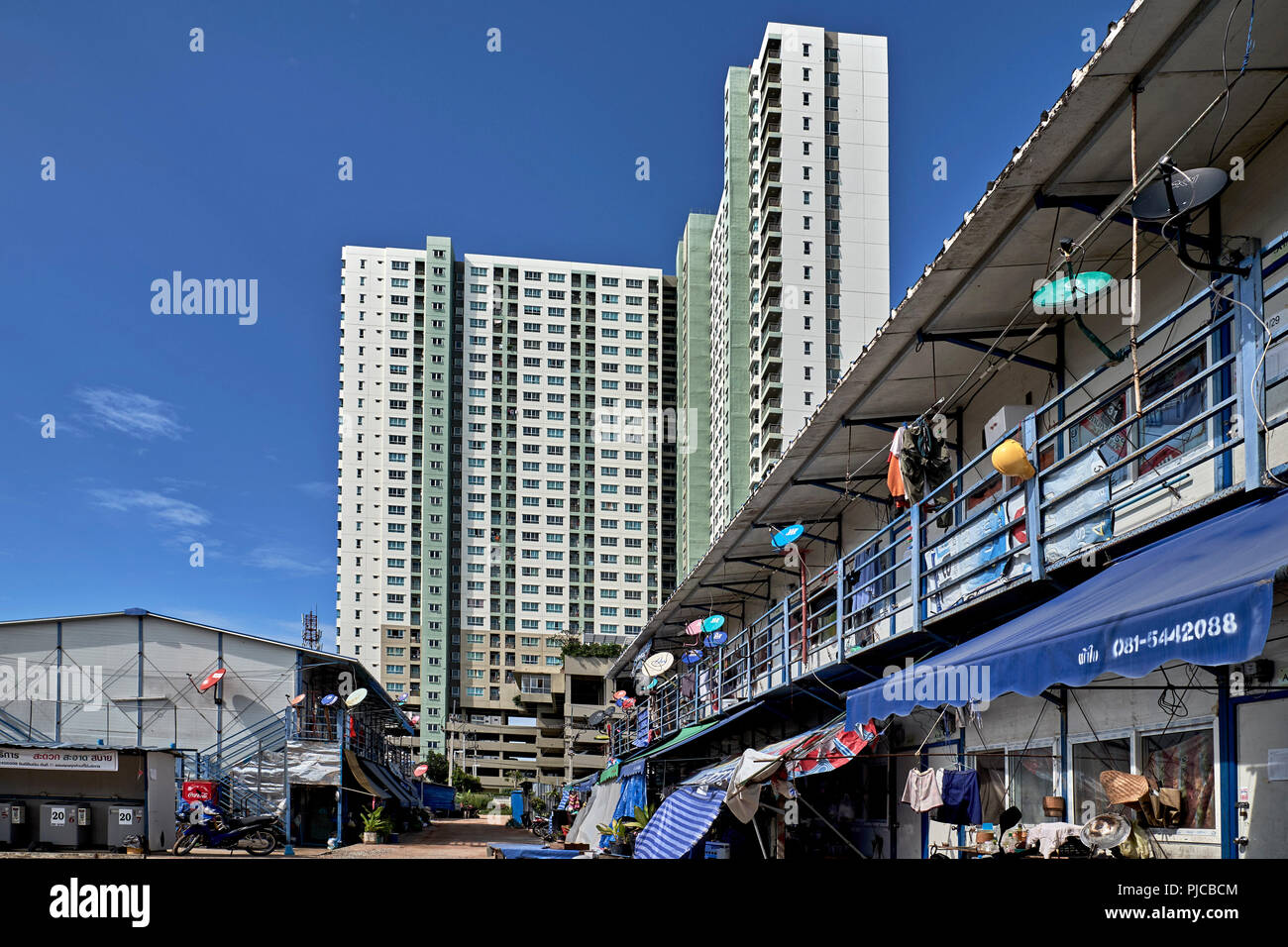 High rise modern apartment block contrasting against old style economy housing giving concept of new v old. Thailand Southeast Asia - Stock Image