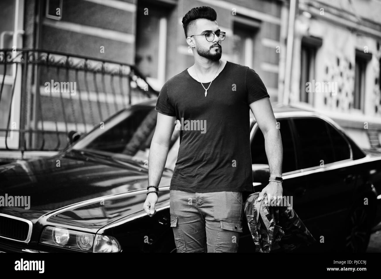Awesome beautiful tall ararbian beard macho man in glasses and black t-shirt walking against business car. - Stock Image