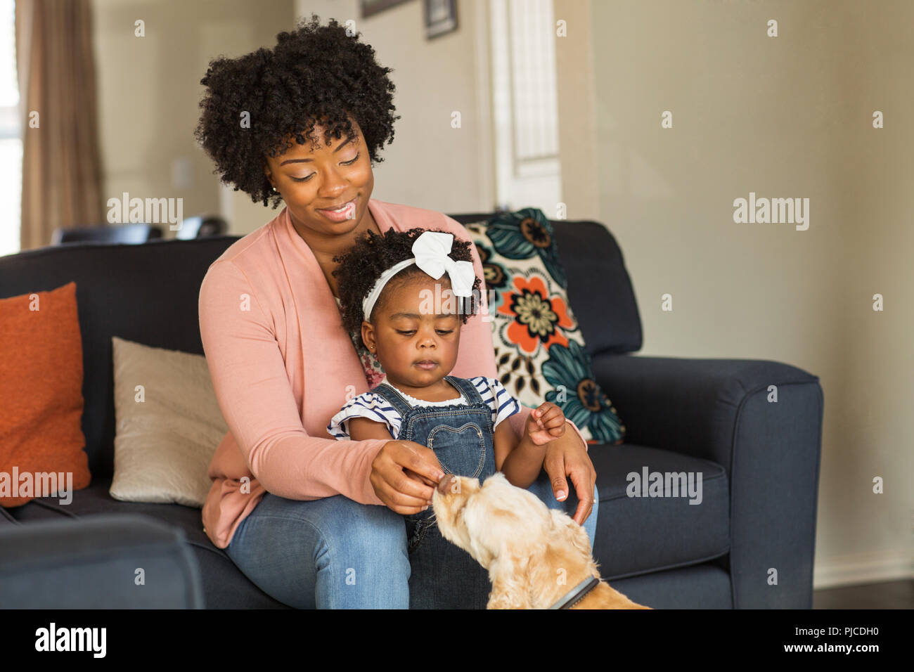 Little girl and her mom playing with thier dog. - Stock Image