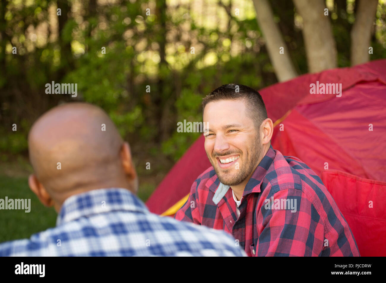 Multi-Ethnic group of friends talking and camping. - Stock Image