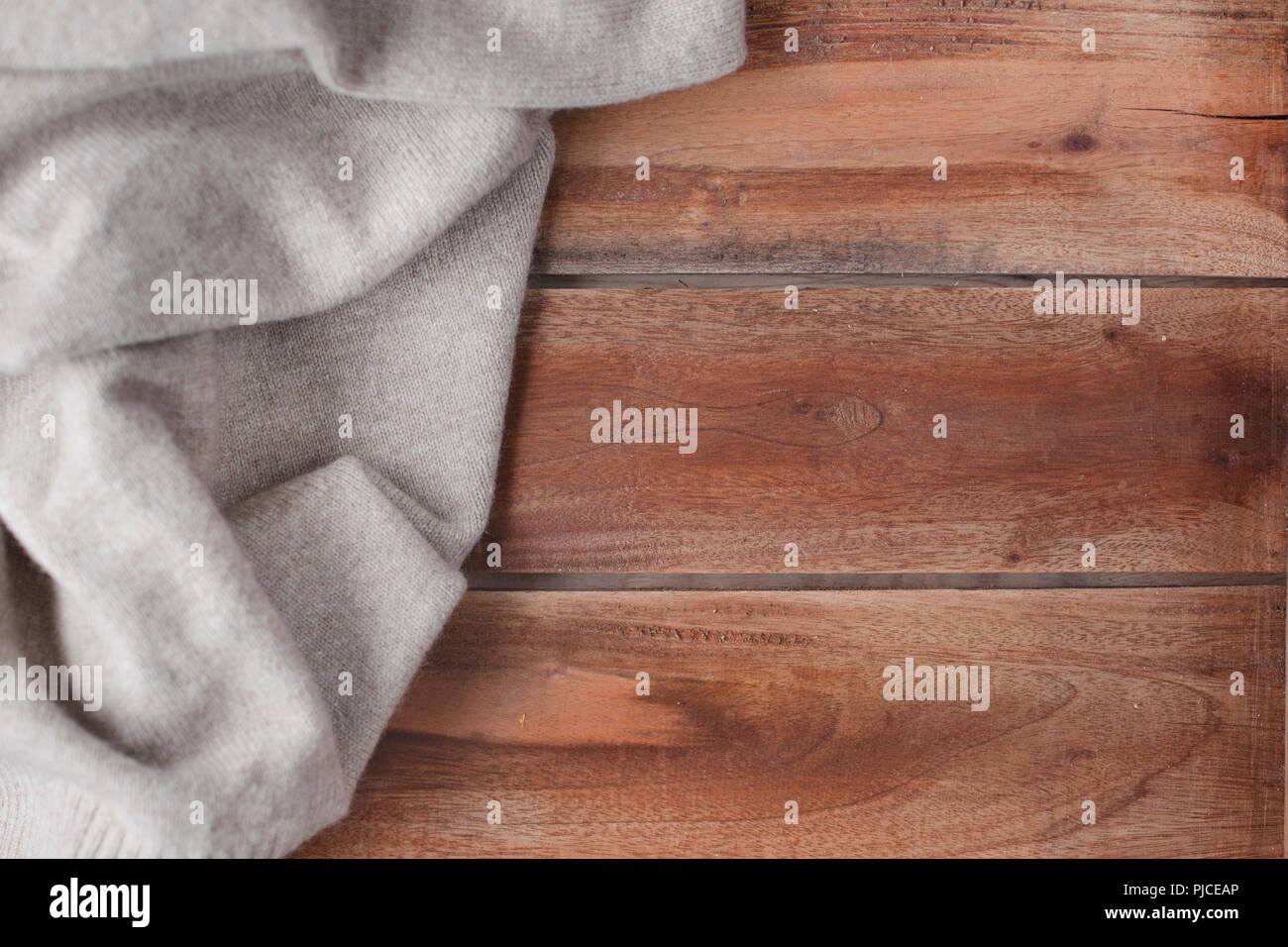 Old wooden background and knitted warm pullover. Autumn decoration and free space for text. Top view.Copy space - Stock Image
