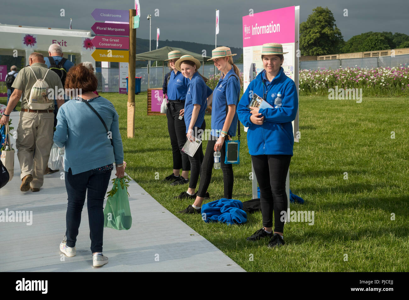 4 young female guides or welcomers stand by information board & smile warmly as visitors walk by - RHS Chatsworth Flower Show, Derbyshire, England, UK - Stock Image