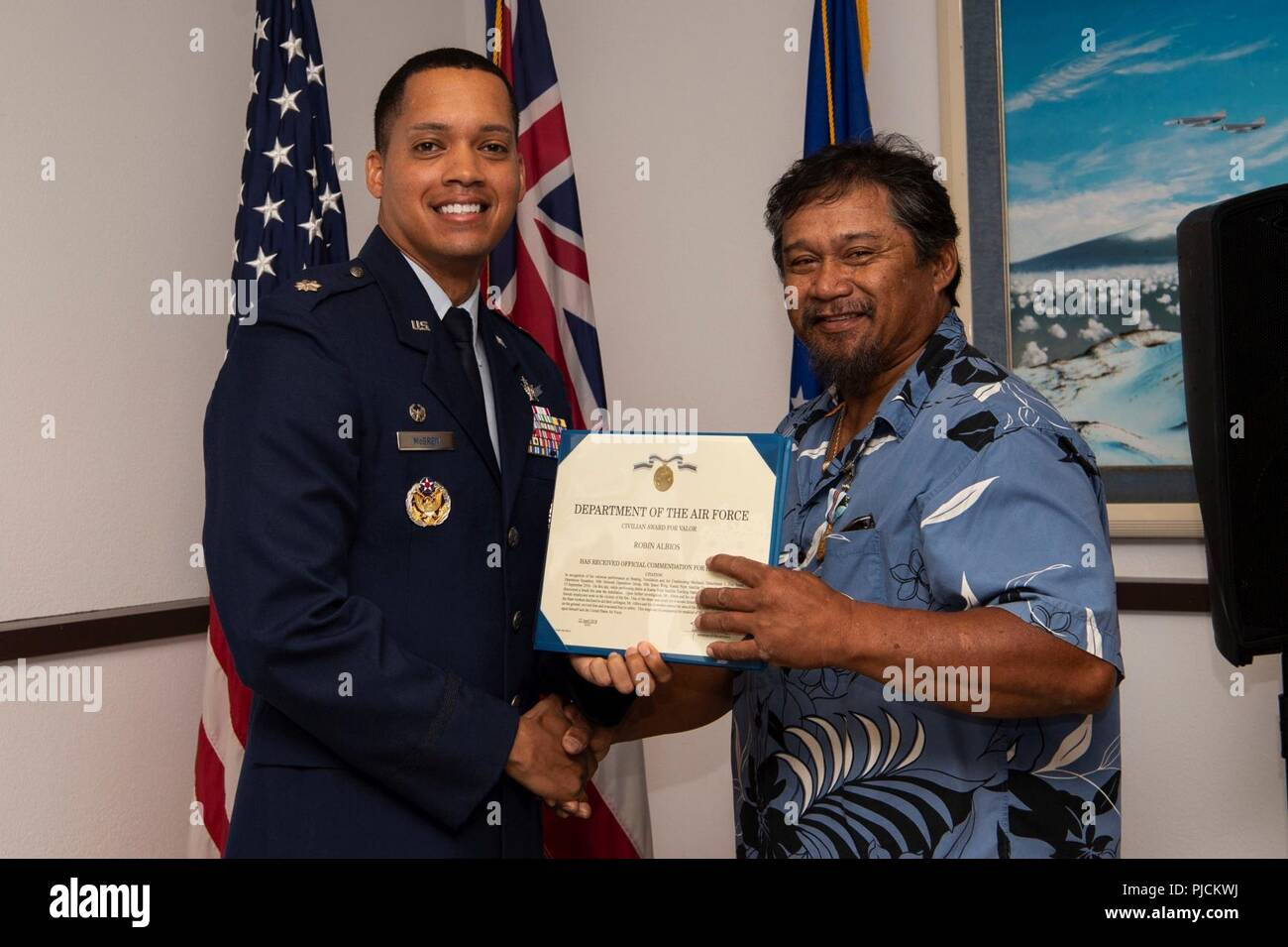 Lt. Col. Wade McGrew, 21st Space Operations Squadron commander, presents the Air Force Civilian Award for Valor to Robin Albios, Detachment 3, 21st SOPS heating, ventilation and air conditioning specialist, at the Kaena Point Satellite Tracking Station, Hawaii, July 23, 2018. Two years ago, Albios provided medical aid to a state of Hawaii volunteer field crew member who suffered from smoke inhalation during a fire at the Kuaokala Game Management Area. - Stock Image