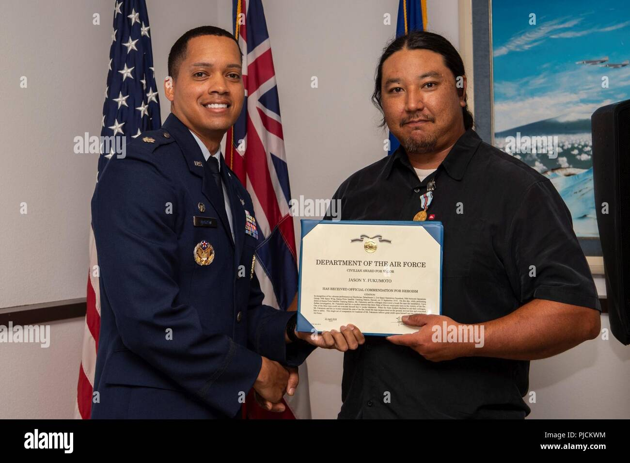 Lt. Col. Wade McGrew, 21st Space Operations Squadron commander, presents the Air Force Civilian Award for Valor to Jason Fukumoto, Detachment 3, 21st SOPS electrician, at the Kaena Point Satellite Tracking Station, Hawaii, July 23, 2018. Two years ago, Fukumoto provided medical aid to a state of Hawaii volunteer field crew member who suffered from smoke inhalation during a fire at the Kuaokala Game Management Area. - Stock Image