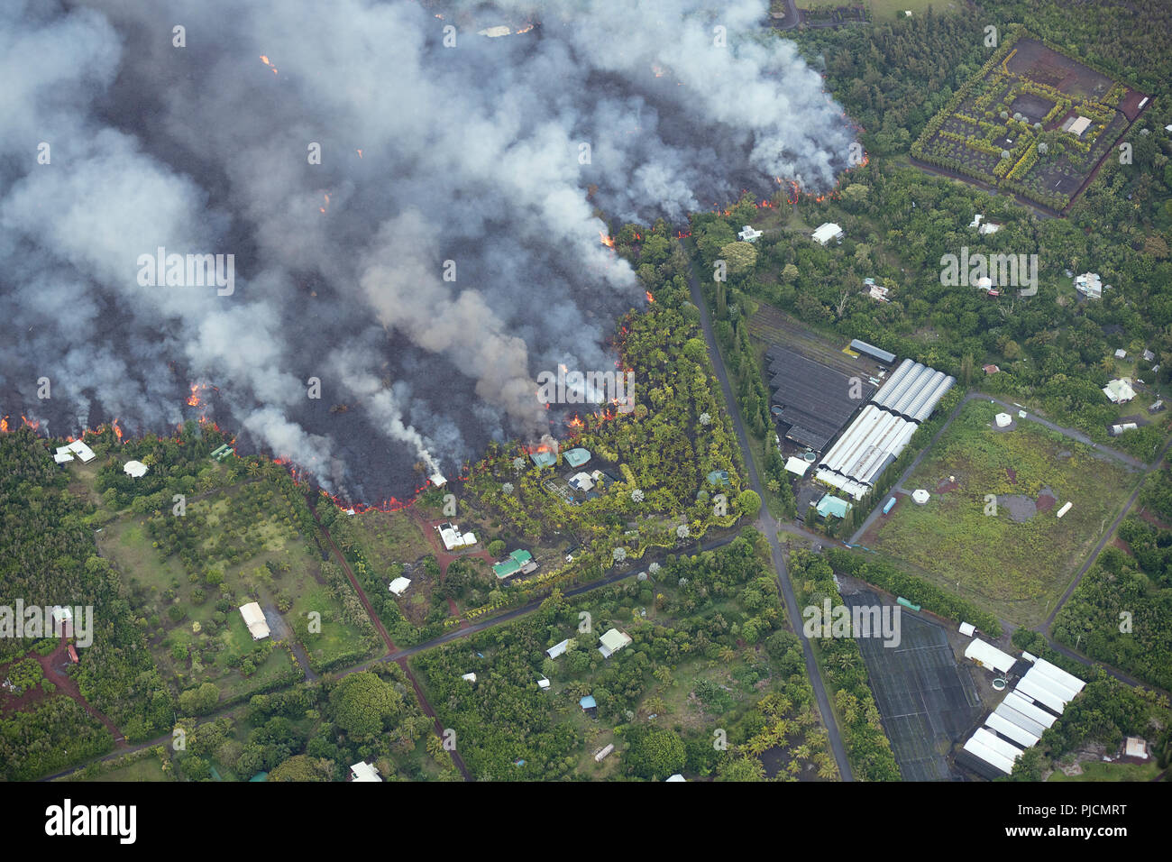 lava originating from Kilauea Volcano, erupting from fissure 8 in Leilani Estates, near Pahoa, flows through lower Puna into Kapoho, destroying agricu - Stock Image