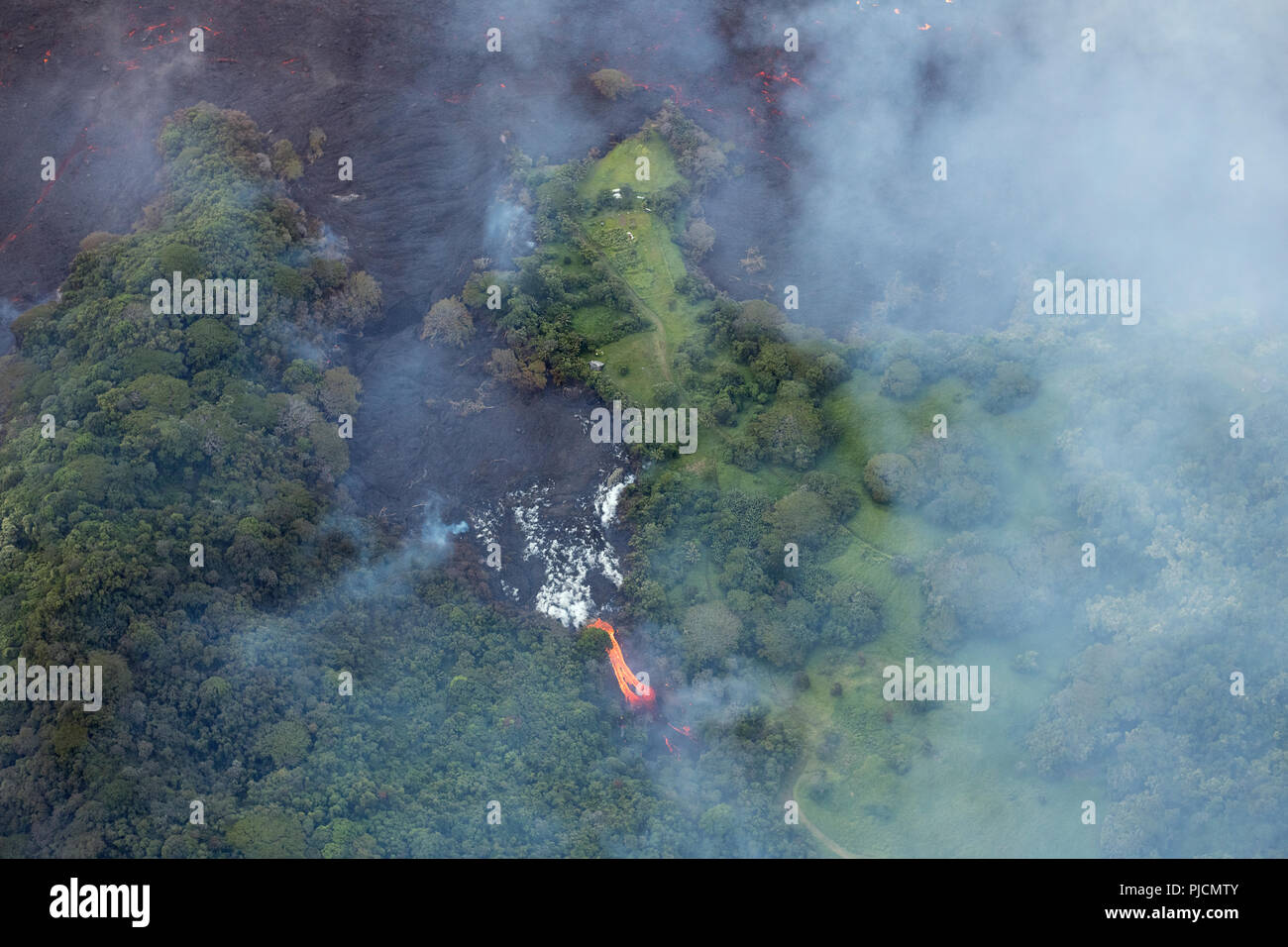 lava originating from Kilauea Volcano, erupting from fissure 8 in Leilani Estates, near Pahoa, flows through lower Puna District into Kapoho, forming  - Stock Image