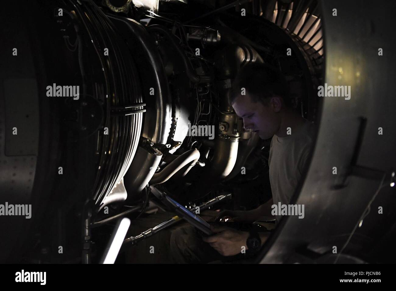 Staff Sgt. Sean Donnelly, 721st Air Mobility Operations Group airlift specialist mission maintenance craftsman, reviews engine schematics during an engine installation of a C-17 Globemaster III aircraft July 19, 2018, at an undisclosed location in Southwest Asia. Donnelly and his fellow 721st AMOG Airmen, who hail from Ramstein Air Base, Germany, delivered the engine and partnered with the 5th Expeditionary Mobility Squadron for the project. - Stock Image