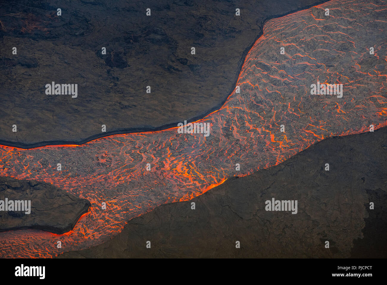 lava erupted from fissure 8 of the Kilauea Volcano east rift zone near Pahoa flows as a glowing river through lower Puna District, Hawaii Island - Stock Image
