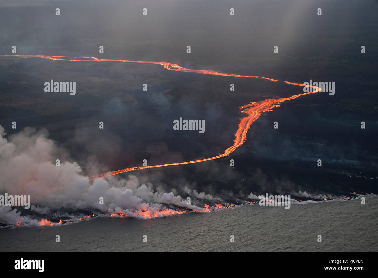 lava erupted from fissure 8 of Kilauea Volcano east rift zone near Pahoa, Hawaii flows as a glowing river through Kapoho to enter the Pacific Ocean. - Stock Image
