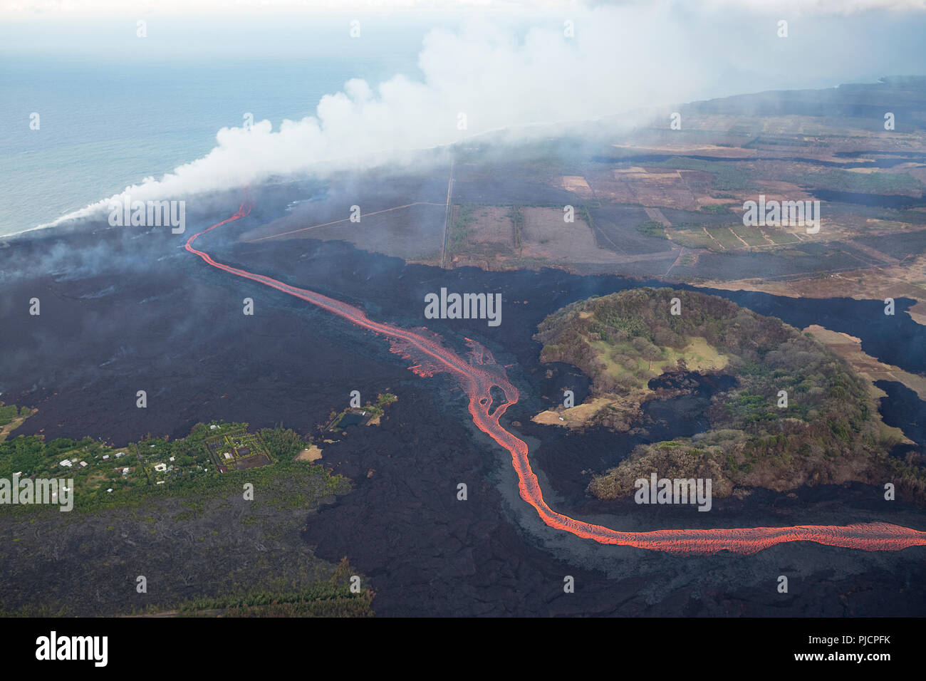 lava erupted from fissure 8 of Hawaii's Kilauea Volcano east rift zone flows as a glowing river around Green Mountain cinder cone to enter the ocean. - Stock Image