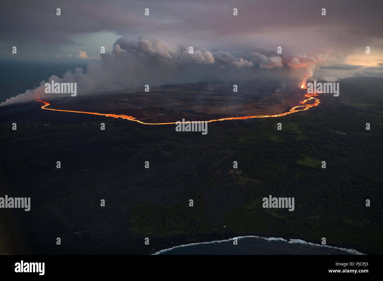 A river of lava flows from Fissure 8 of Hawaii's Kilauea Volcano (at right) through lower Puna to enter the ocean, releasing a cloud of acidic steam. - Stock Image