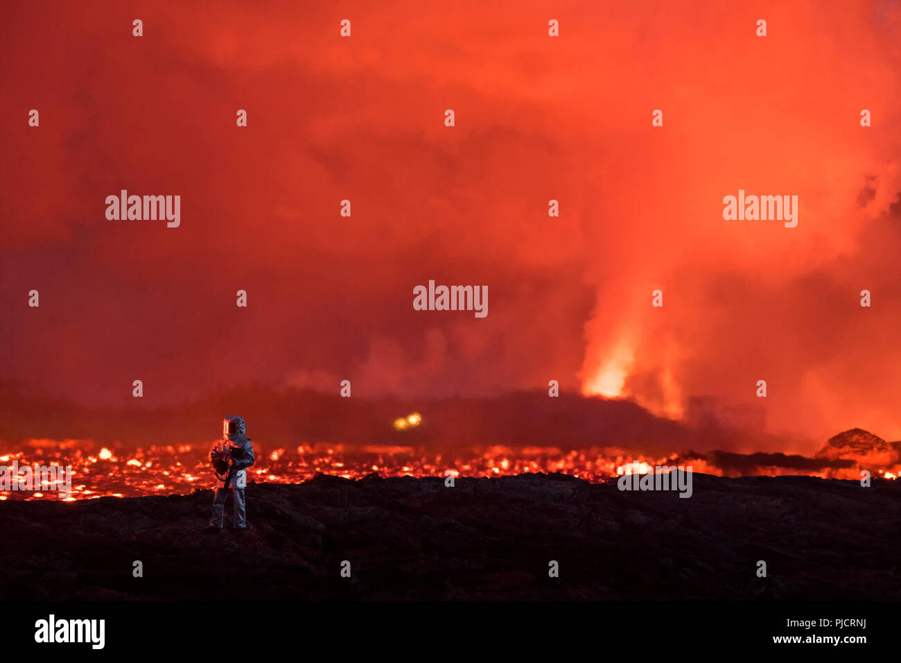 a firefighter tests heat protective gear next to a glowing river of hot lava erupting from fissure 8 (in background) of Kilauea Volcano east rift zone - Stock Image