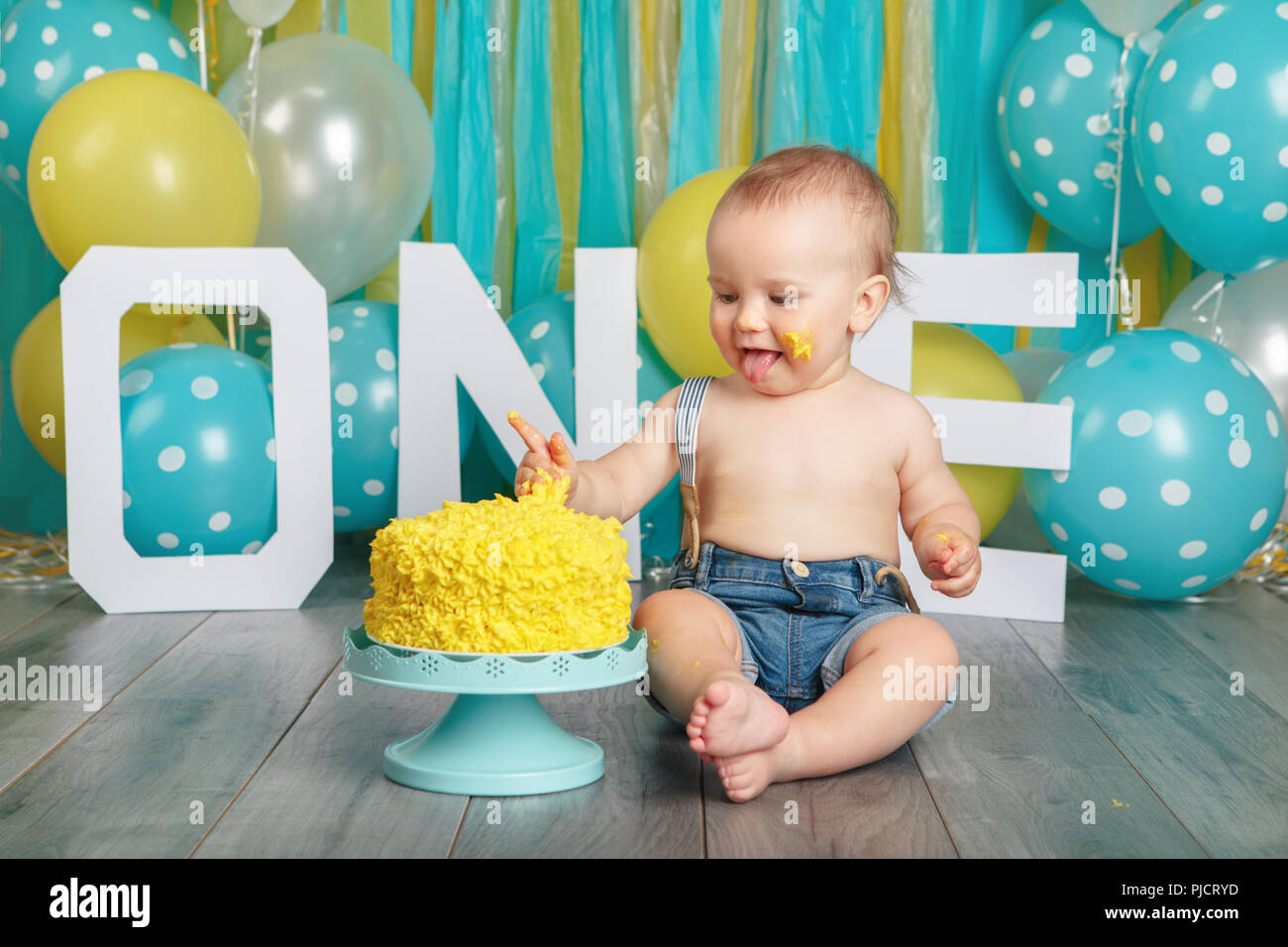 Portrait Of Cute Adorable Caucasian Baby Boy In Jeans Pants Celebrating His First Birthday Cake Smash Concept Child Kid Sitting On Floor Studio E