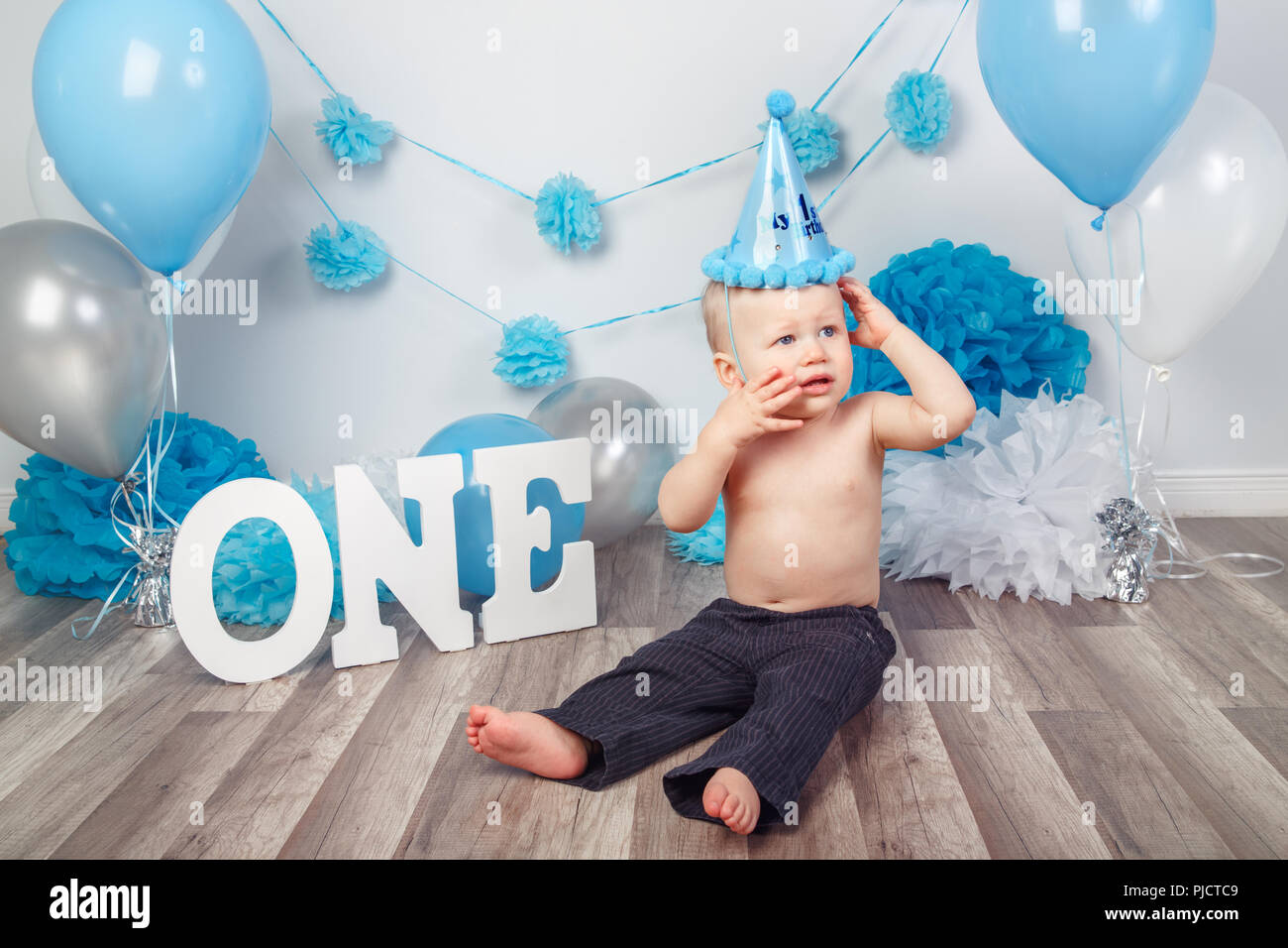 Portrait Of Adorable Caucasian Baby Boy With Blue Eyes In Dark Pants And Cone Hat Celebrating His First Birthday Letters One Balloons On Backgrou